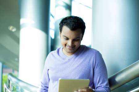 captivated: Closeup portrait, young captivated, absorbed, smiling man in purple sweater perusing, pondering emails on silver gray tablet touch-pad, isolated indoors office background Stock Photo