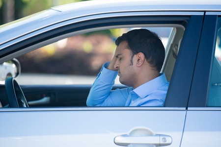 Closeup portrait, angry young sitting man pissed off by drivers in front of him, hand on head, isolated city street background. Road rage traffic jam concept