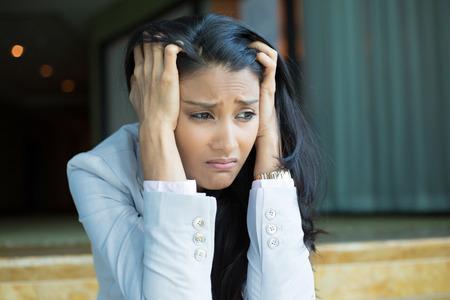 nešťastný: Detailním portrét, smutný mladá žena v bílém šedém obleku sedí na schodech, opravdu depresivní, dolů o něčem, izolovaný v interiéru úřadě pozadí. Negativní emoce mimika pocit reakce
