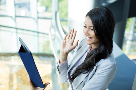 woman in suit: Closeup side view portrait, attractive woman in gray business suit waving saying hi gesture on tablet, isolated indoors office background Stock Photo