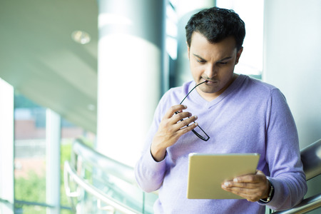 indian business man: Closeup portrait, young captivated, absorbed, engrossed man in purple sweater biting black eye glasses, perusing, pondering emails on silver gray tablet touch-pad, isolated indoors office background Stock Photo