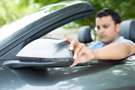 Close up retrato, jovem piloto homem que olha ajustando espelho lateral do carro vista, certificando-se que ele pode ver o tr