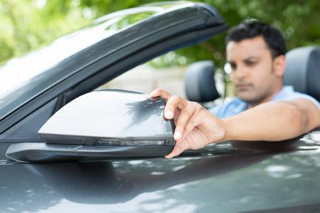chofer: Primer retrato, conductor hombre joven que busca ajustar espejo lateral opini�n del coche, asegur�ndose de que pueda ver el tr�fico OK a su alrededor, el fondo aislado al aire libre Foto de archivo