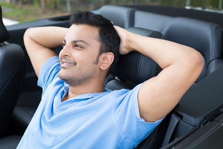 Closeup portrait, happy young smiling handsome man in blue polo in his new black sports car, relaxing, resting head on arms, isolated on outdoors background with vehicle. Stock Photo