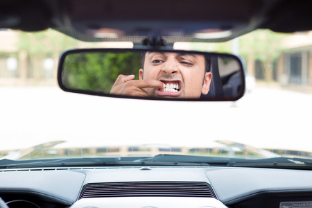bad hygiene: Closeup portrait, funny young man driver looking at rear view mirror to pick teeth with finger nails because of food stuck behind in between, isolated interior car windshield background Stock Photo