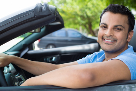 Closeup portrait, happy young smiling handsome man in blue polo shirt in his new black sports car, relaxing, looking at camera, isolated on outdoors background with vehicle and green trees. Stock Photo