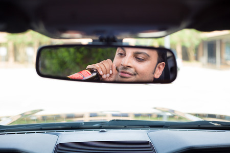 under the influence: Closeup portrait, young guy drinking alcoholic beverage stoned, under the influence,  isolated interior car windshield background. A menace driver to the road Stock Photo