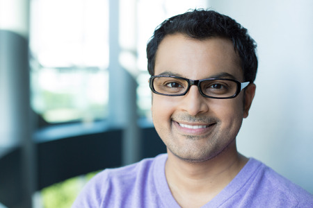 Closeup headshot portrait, smiling happy handsome man in purple sweater v-neck, wearing black glasses, isolated inside office background. Stock Photo