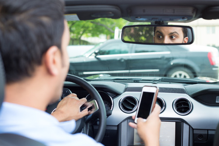 Closeup portrait, young man in blue polo shirt driving in black car and checking his phone, then shocked almost about to have traffic accident, isolated interior car windshield background 免版税图像