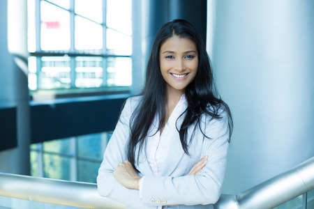 hispanic students: Closeup portrait, young professional, beautiful confident woman in pink shirt gray suit, arms crossed folded, smiling isolated indoors office background. Positive human emotions