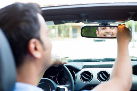 Closeup portrait, happy young man driver looking at rear view mirror smiling, adjusting image reflection, isolated interior car windshield background. Positive human expression body language