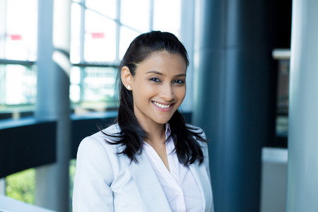 mexican woman: Closeup portrait, young professional, beautiful confident woman in gray white suit, friendly personality, smiling isolated indoors office background. Positive human emotions Stock Photo