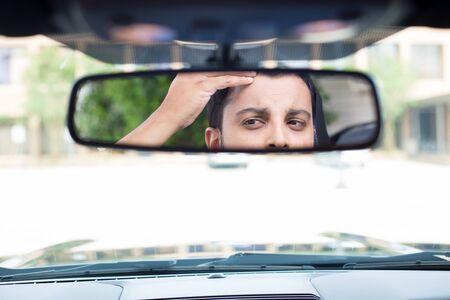 mirror?: Primer retrato, conductor joven divertido mirar el espejo retrovisor mirando la caída del cabello emite pico de viuda o preocupado, aislado fondo interior del parabrisas del coche