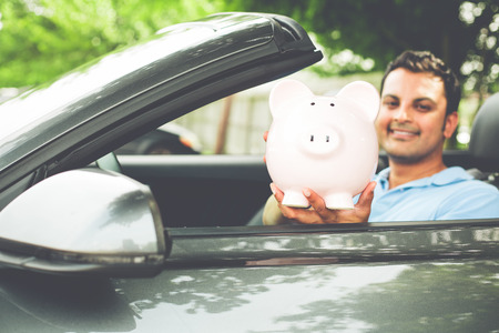Closeup portrait, handsome young man in blue polo shirt showing pink piggy bank inside new sports car, isolated outdoors background.  Happy to have good low apr interest rates, finance rebate deals