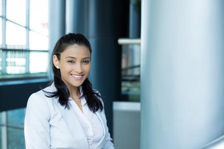 gestion empresarial: Primer retrato, joven profesional mujer hermosa, confía en traje blanco gris, personalidad amable, sonriente aislados en el interior fondo de la oficina. Emociones humanas positivas