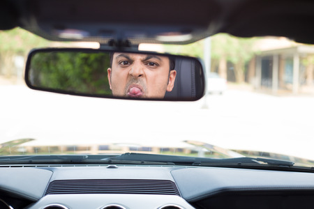 Closeup portrait, angry young driver making stupid faces in rearview mirror reflection and sticking out tongue.  Infuriated road rage concept, isolated interior car windshield background