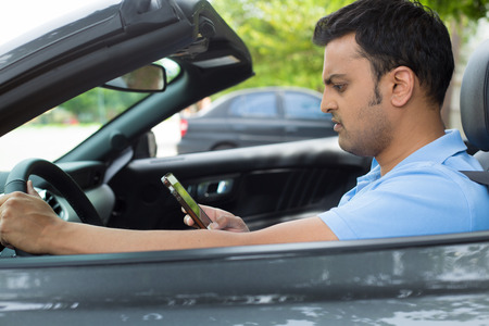 Closeup portrait, young man driving in black gray sports car and checking his phone, annoyed by navigation gps system or bad text message or email, isolated outdoors background