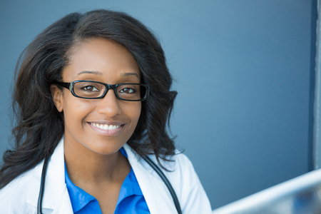 american staff: Closeup headshot portrait of friendly, smiling confident female healthcare professional with lab coat, glasses, and stethoscope. Isolated hospital clinic background. Time for an office visit Stock Photo