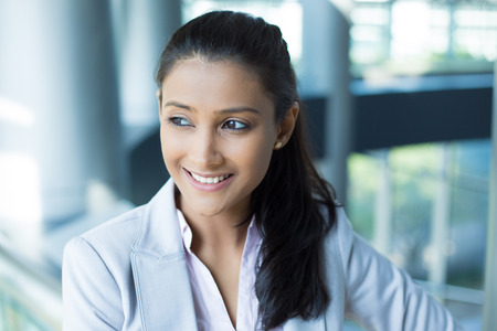 mexican girl: Closeup portrait, charming upbeat smiling joyful happy young woman looking side and down daydreaming something nice, isolated indoors office background. Positive human facial expressions feelings