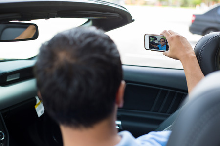 roadster: Closeup portrait, happy fun young man holding phone taking picture of himself in brand new sports car, isolated outdoors outside background