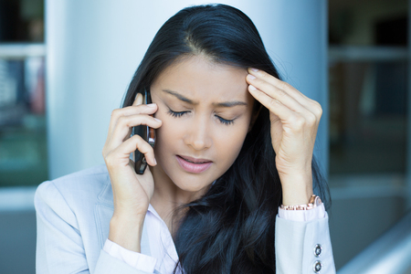 migraine: Closeup portrait, sad, depressed, unhappy worried young woman talking on phone,  isolated indoors office background. Negative human emotions, facial expressions, feelings, reaction. Bad news.