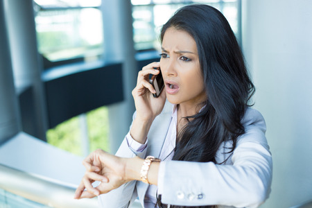 running out of time: Closeup portrait, young woman in gray business suit blazer talking on cell phone concerned about running out of time on watch, isolated indoors office background