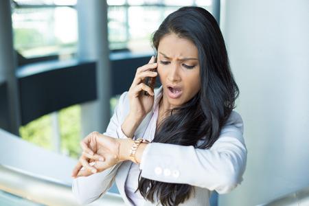 Portrait Gros plan, jeune femme en costume gris d'affaires Blazer parlant au téléphone cellulaire préoccupés à court de temps sur la montre, à l'intérieur isolés bureau fond