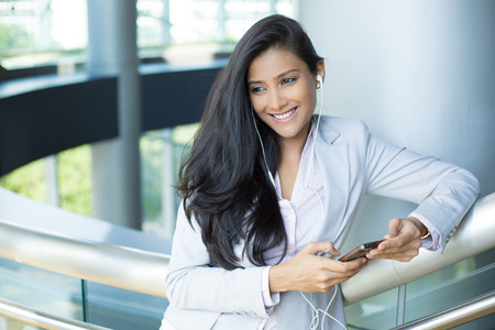 listening: Closeup portrait, young happy business woman in gray white suit dress standing, checking her cellphone, listening to music, isolated on indoors office background. Corporate life success.