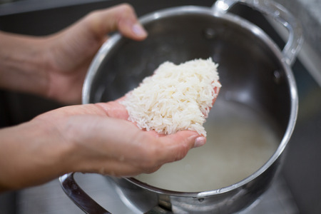 Closeup portrait of hands washing jasmine rice to free from dust and dirt before cooking, isolated background of sink Foto de archivo