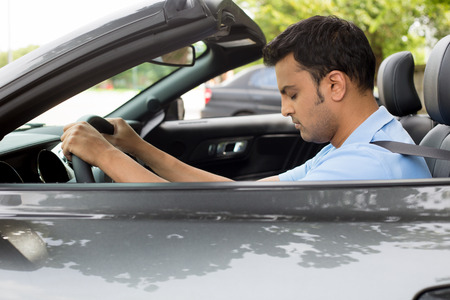 long hours: Closeup portrait tired young handsome man with short attention span, driving his car after long hours trip, trying to stay awake at wheel, isolated outside background. Sleep deprivation Stock Photo