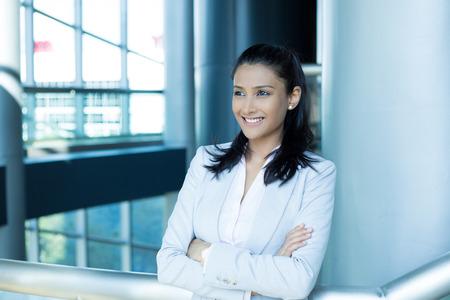 profesionistas: Primer retrato, joven profesional hermosa mujer, confiado en juego rosado camisa gris, con los brazos cruzados doblado, sonriente aislados en el interior fondo de la oficina. Emociones humanas positivas