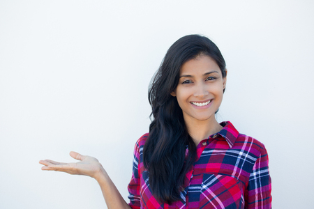 Closeup portrait happy confident young smiling woman gesturing, presenting space at left with palm up isolated white wall background. Positive human emotion signs symbol, facial expression feelings