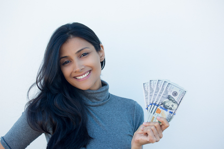 financial reward: Closeup portrait, excited successful young business woman in gray shirt holding money dollar bills in hand, isolated white wall background. Positive emotion facial expression feeling. Financial reward
