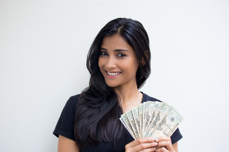 Closeup portrait, excited successful young business woman in black shirt holding money dollar bills in hand isolated white wall background. Positive emotion facial expression feeling. Financial reward Stock Photo