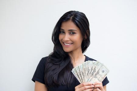 efectivo: Primer retrato, excitado joven mujer de negocios exitosa en camisa negro sosteniendo facturas de dinero en d�lares en el fondo aislado pared blanca mano. Emoci�n positiva sensaci�n de la expresi�n facial. Recompensa financiera