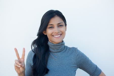Closeup portrait, young, happy, smiling, confident, excited woman giving peace victory, two sign gesture, isolated white wall background. Positive emotion facial expression feelings symbols, attitude Imagens