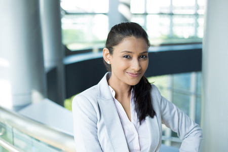 smirking: Closeup portrait, charming upbeat smiling joyful happy young woman smirking, thinking daydreaming something nice, isolated indoors office background. Positive human facial expressions feelings