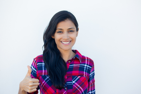 Closeup portrait of young pretty woman with one thumbs up sign gesture, plaid red shirt, isolated white wall background. Positive emotion facial expression feelings, signs and symbols, body language Archivio Fotografico