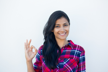 Closeup portrait of young happy, smiling excited beautiful natural woman in plaid red shirt giving OK sign with fingers, isolated white wall background. Positive facial expressions symbols Archivio Fotografico