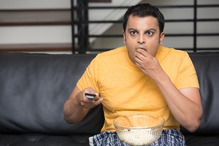 tv: Portrait Gros plan, jeune homme en t-shirt jaune, assis sur un canapé en cuir noir, regarder la télévision, tenant à distance, surpris de ce qu'il voit, grignotant du pop-corn, fond isolé intérieur plat Banque d'images