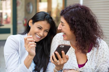 Close-up portret van twee verrast meisjes kijken naar mobiele telefoon, het bespreken laatste roddels nieuws, het delen van intieme momenten, winkelen, lachen om wat ze zien, geïsoleerde buitenshuis achtergrond Stockfoto - 48103435