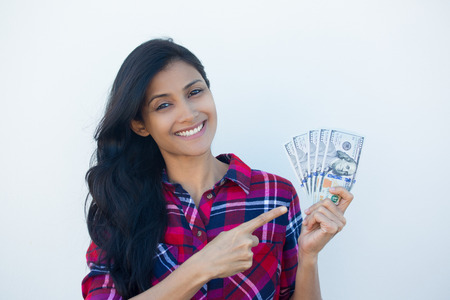 indian girl: Closeup portrait, excited successful young business woman in plaid shirt holding money dollar bills in hand isolated white wall background. Positive emotion facial expression feeling. Financial reward Stock Photo