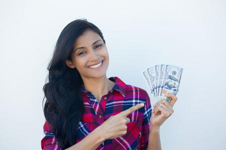 fille indienne: Portrait Gros plan, le succès excité jeune femme d'affaires en chemise à carreaux tenant factures de l'argent en dollars dans la main isolé mur blanc arrière-plan. L'émotion positive du visage sentiment d'expression. Récompense financière Banque d'images