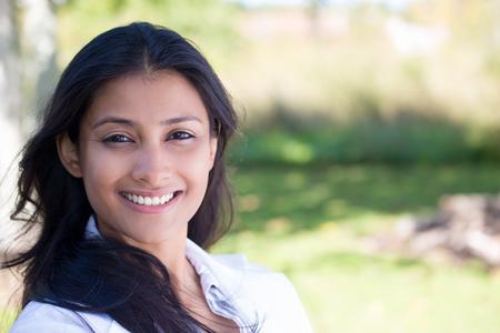 actitud: Primer retrato de confianza sonriente mujer bastante joven feliz en traje gris, fondo aislado de árboles borrosas. Positivos emoción humana sentimientos de expresión facial, la actitud, la percepción