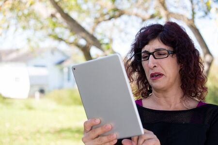 large woman: Closeup portrait, upset young woman with curly black hair, astonished surprised,  large eyes in black glasses by what she sees on her gray silver tablet pad, isolated outdoors background.