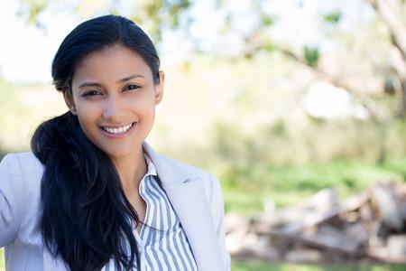 attitude: Primer retrato de confianza sonriente mujer bastante joven feliz en traje gris, fondo aislado de árboles borrosas. Positivos emoción humana sentimientos de expresión facial, la actitud, la percepción