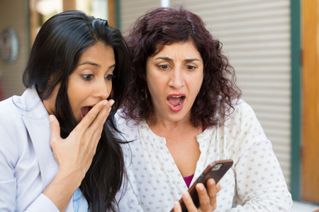 Closeup portrait two surprised girls looking at cell phone discussing latest gossip news, shopping, flabbergasted at what they see, isolated outdoors background