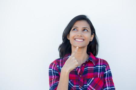 mujer enamorada: Primer retrato, optimista encantadora sonrisa alegre mujer joven feliz mirando hacia arriba soñando algo agradable, aislado de fondo de pared blanca. Emociones humanas positivas expresiones faciales sentimientos