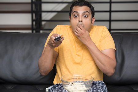 munching: Closeup portrait, young man in yellow t-shirt, sitting on black leather couch, watching TV, holding remote, surprised at what he sees, munching popcorn, isolated indoors flat background