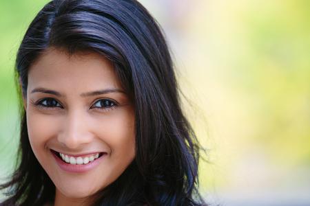 Closeup headshot portrét jistý, usmíval se šťastný hezká mladá žena, izolované pozadí rozmazaných stromů. Pozitivní lidské emoce mimika pocity, postoje, vnímání